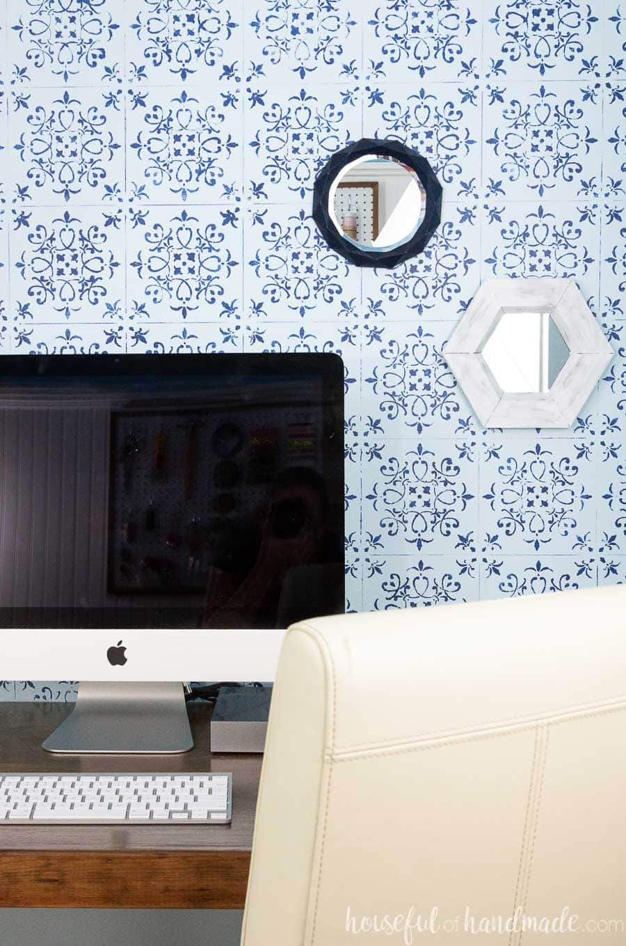White rustic hexagon wall mirror and navy geometric mirror on a wall behind a computer.