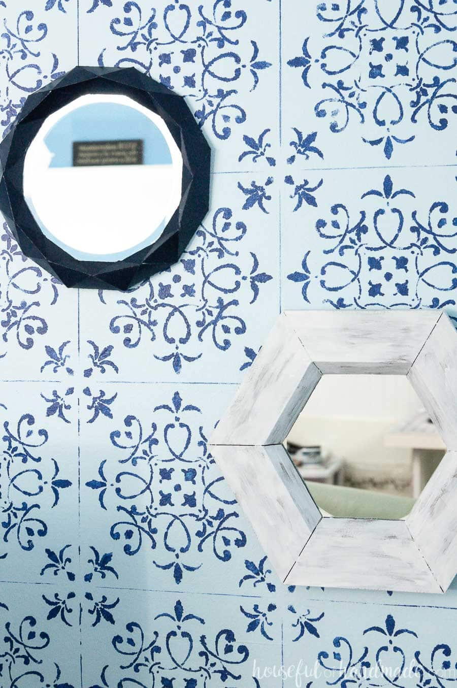 Close up of the small decorative mirrors on a blue and navy stenciled wall.