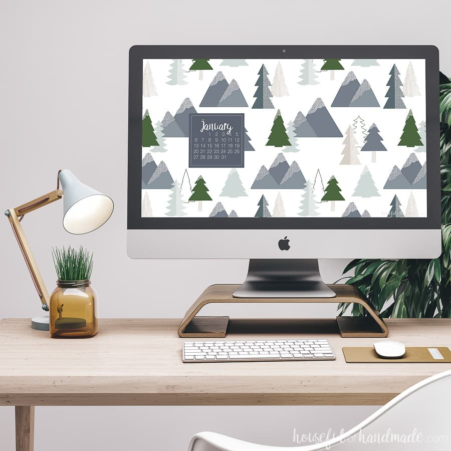 Desktop computer on a desk showing the free digital backgrounds for January on the screen.