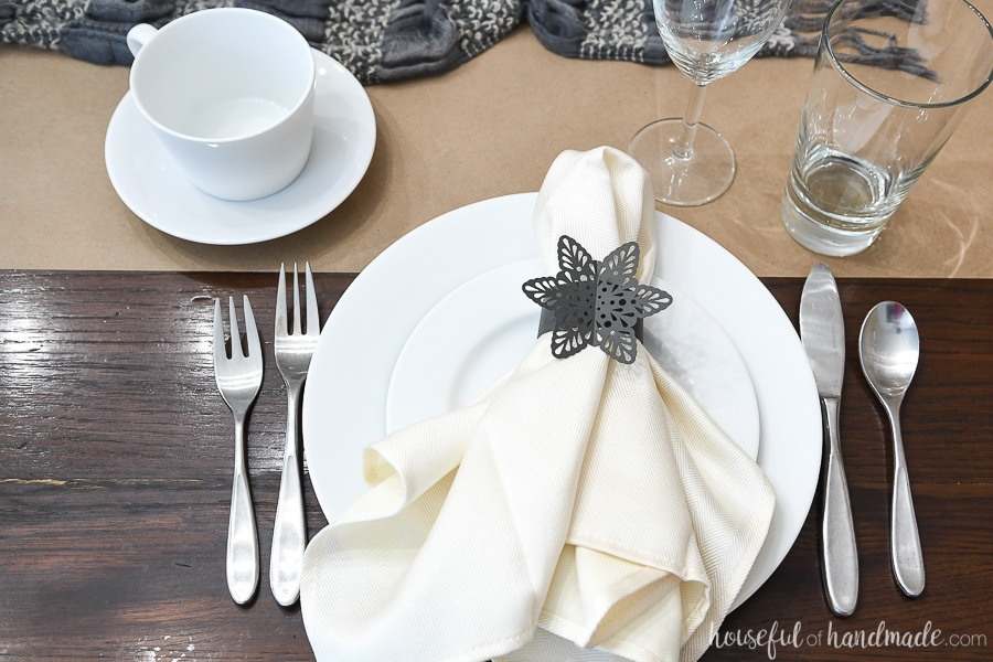 Winter table setting with paper snowflake napkin rings and mugs.
