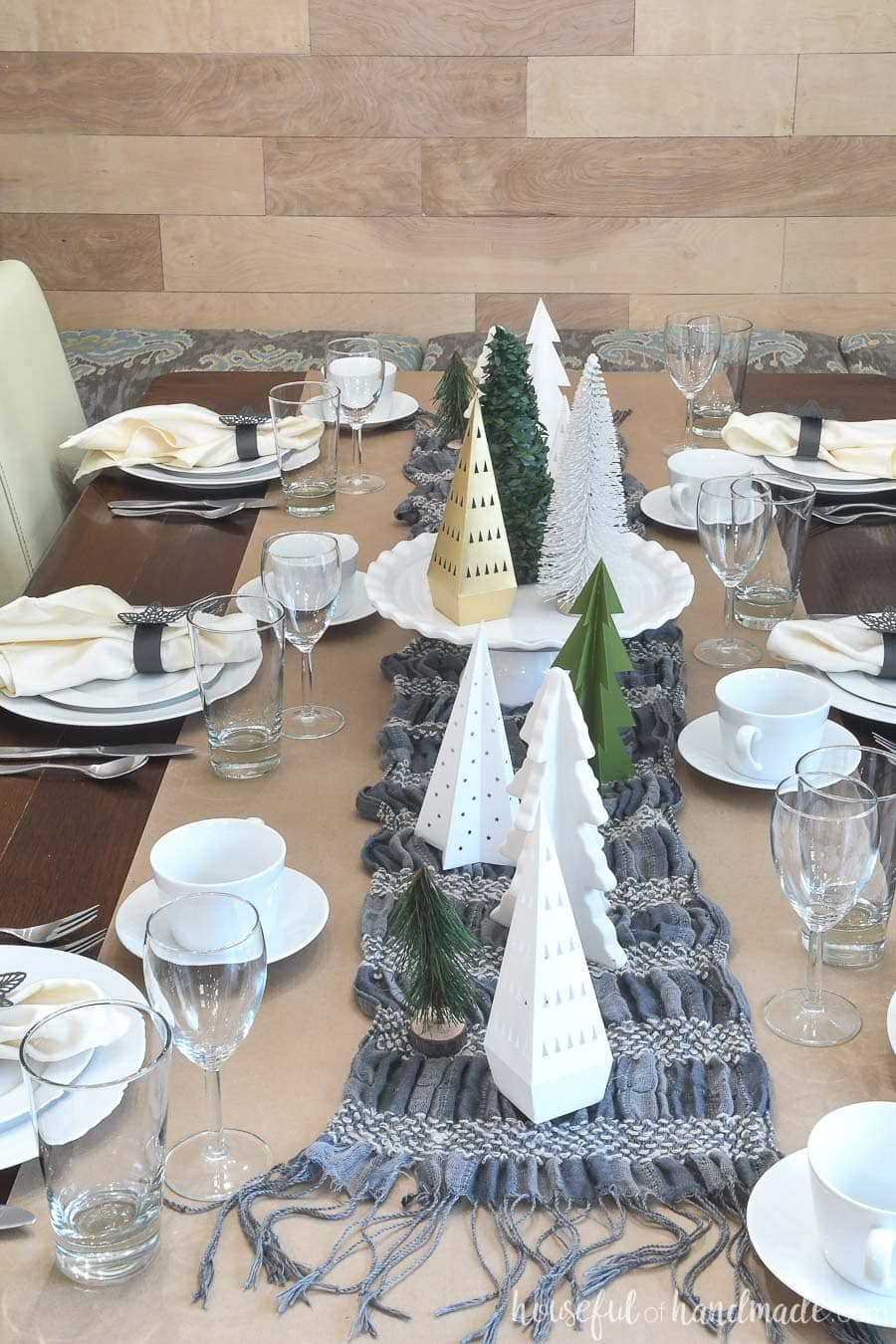 Papercraft winter tablescape with brown paper, a winter scarf, and trees made from paper.