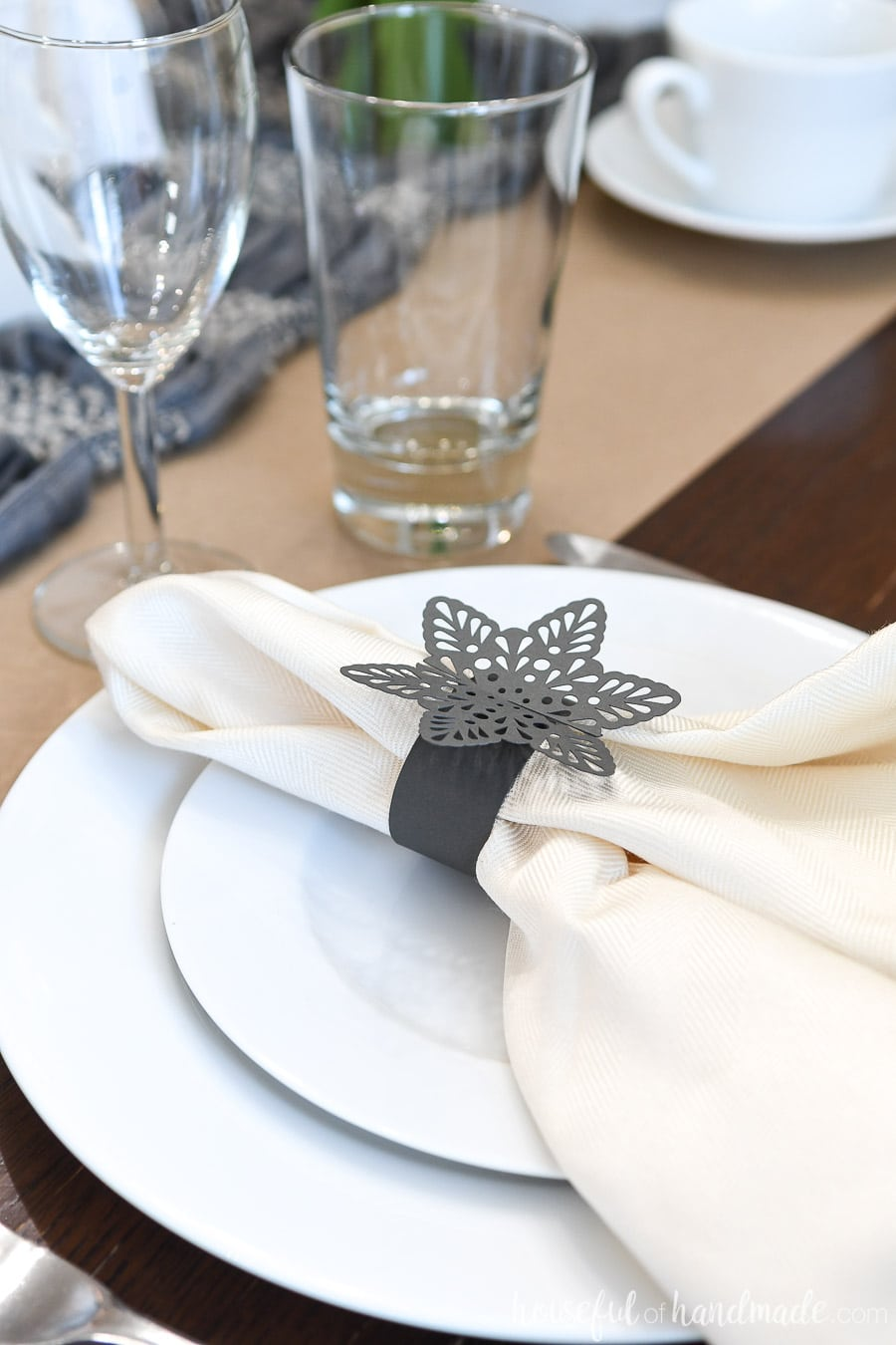 Close-up view of the table setting on the winter tablescape with snowflake paper napkin rings on the plates.