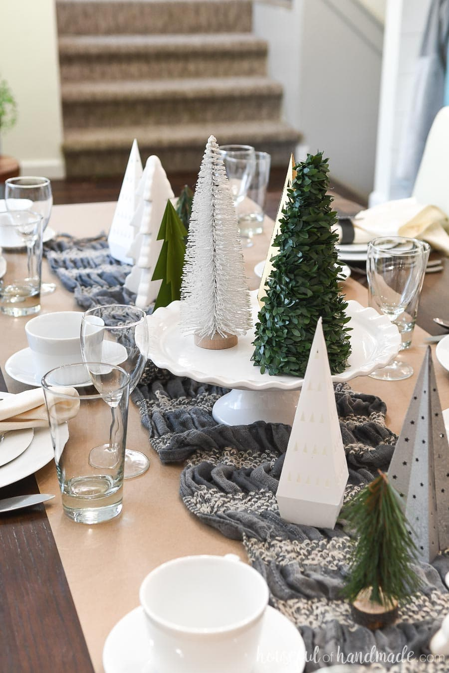 Paper Christmas trees decorating the centerpiece of a winter table.