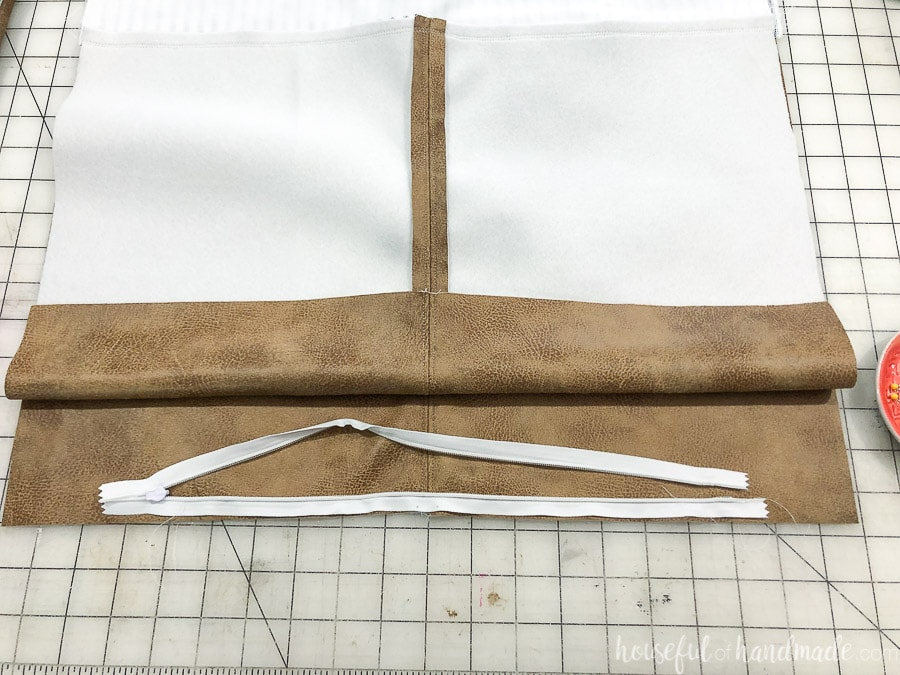 One half of the invisible zipper sewed to the DIY leather pillow cover and figuring out how to properly attach the other side.