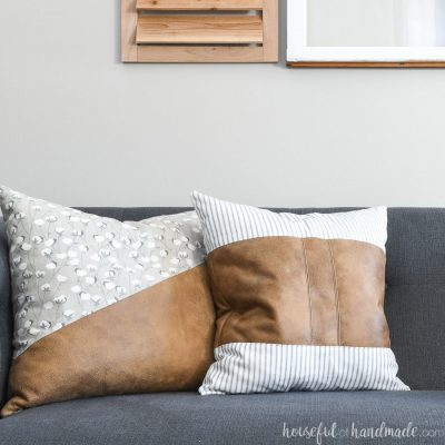 Two decorative leather pillow covers on a sofa.