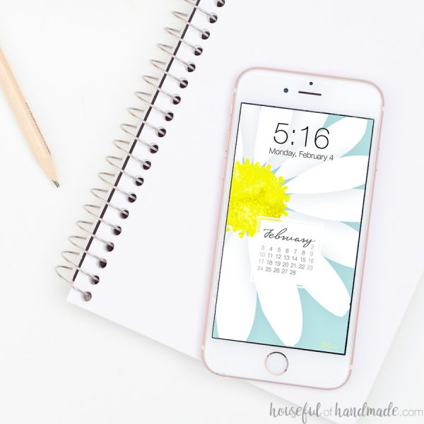 Square photo of iPhone with digital wallpaper on it that you added a calendar to with Canva.