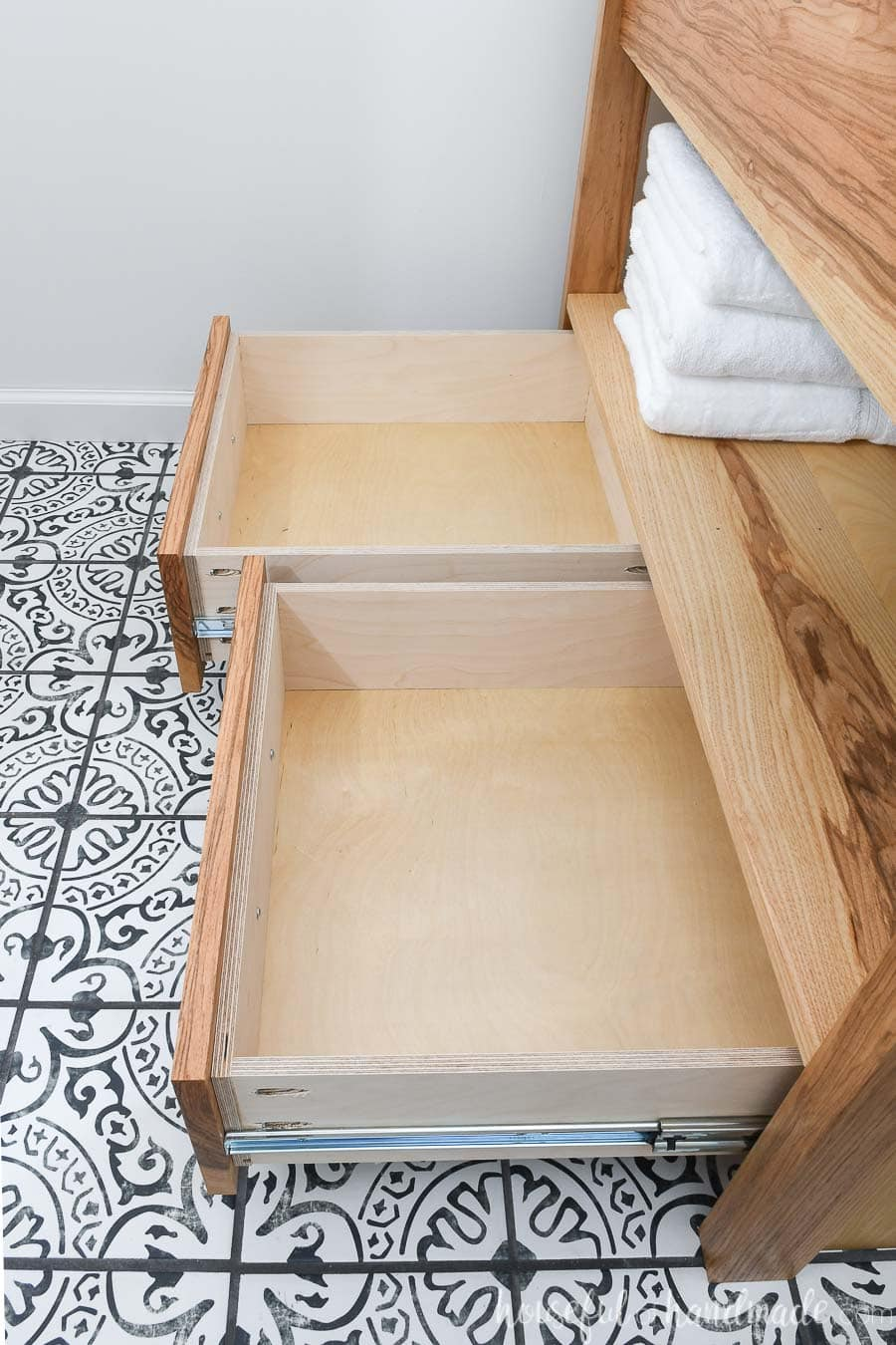 Drawers of the modern bathroom vanity open showing the storage space.