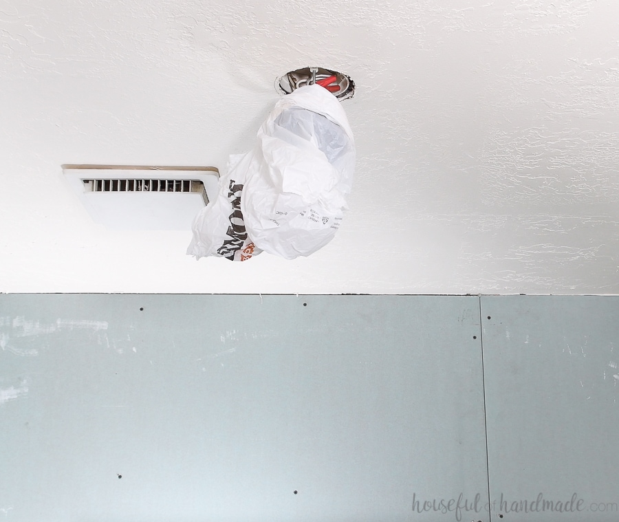 Prepping the ceiling by lowering the fixtures before painting.