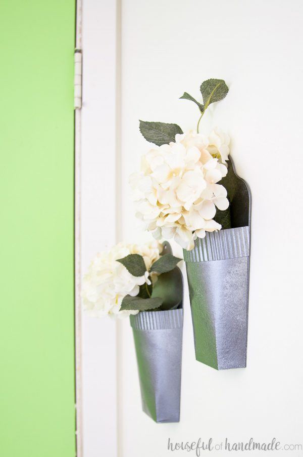 Side view of the DIY wall vases hanging on the wall filled with white hydrangea flowers.