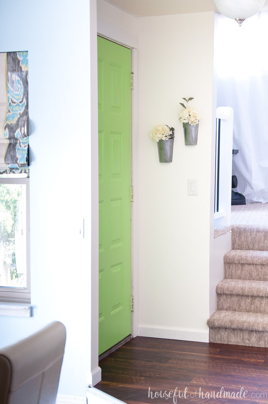 Entryway in the home with green door and faux metal wall vases hanging on the wall.