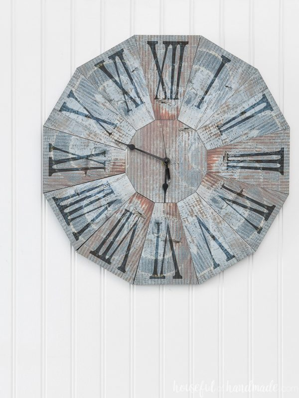 Rusted metal textured clock made out of paper hanging on a white wall.