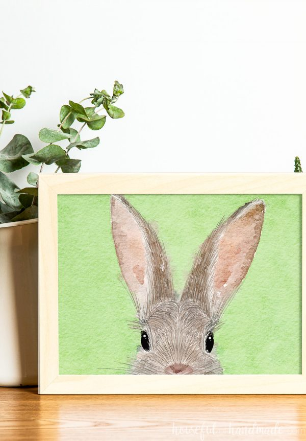 Easter printable of a bunny face drawn on a green watercolor background.