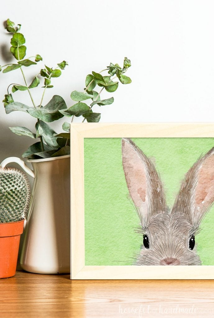 Printable bunny art in a frame in front of a vase of eucalyptus.