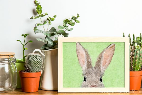 Line of potted plants with a picture of bunny art in a frame.
