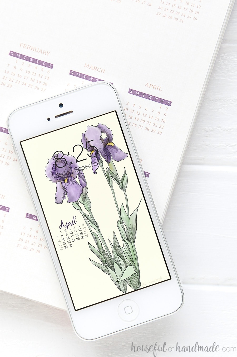 White iPhone with iris wallpaper on the background on top of a planner.