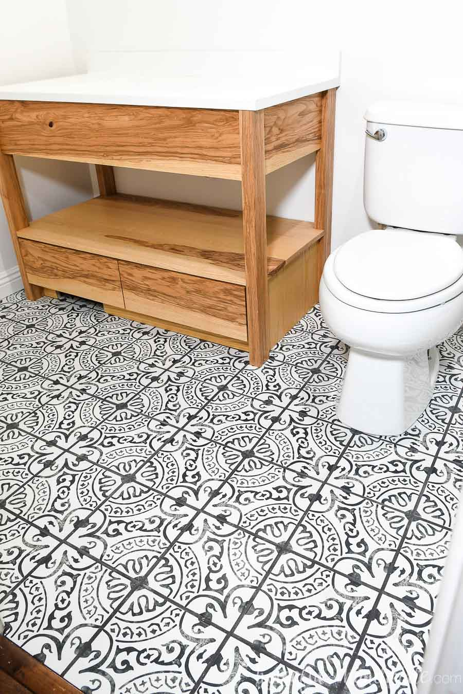 Bathroom with ash wood vanity and black and white porcelain floor tiles.