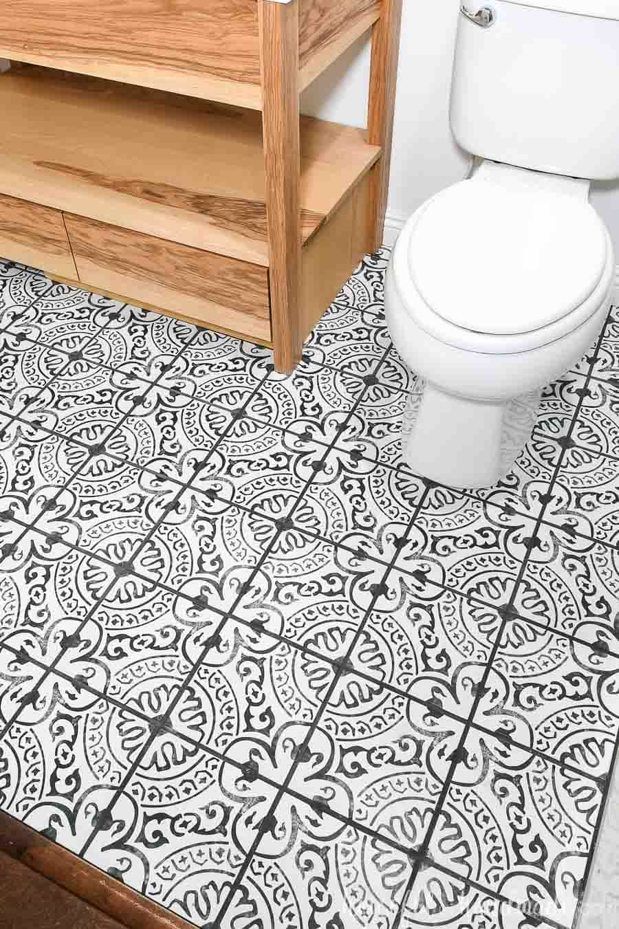 Floor tiled with black and white patterned tiles with black grout.