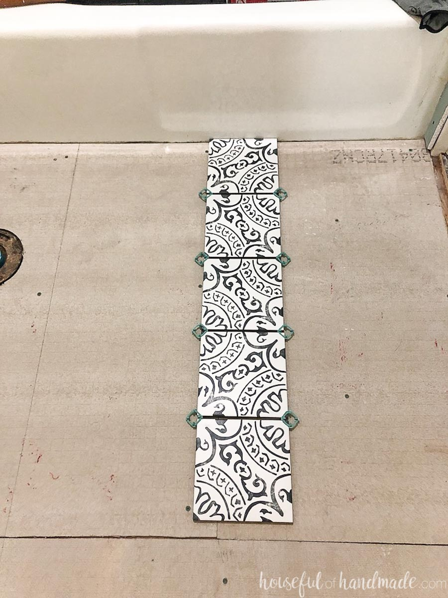 Row of tiles in a dry layout of patterned floor tiles before installing them.