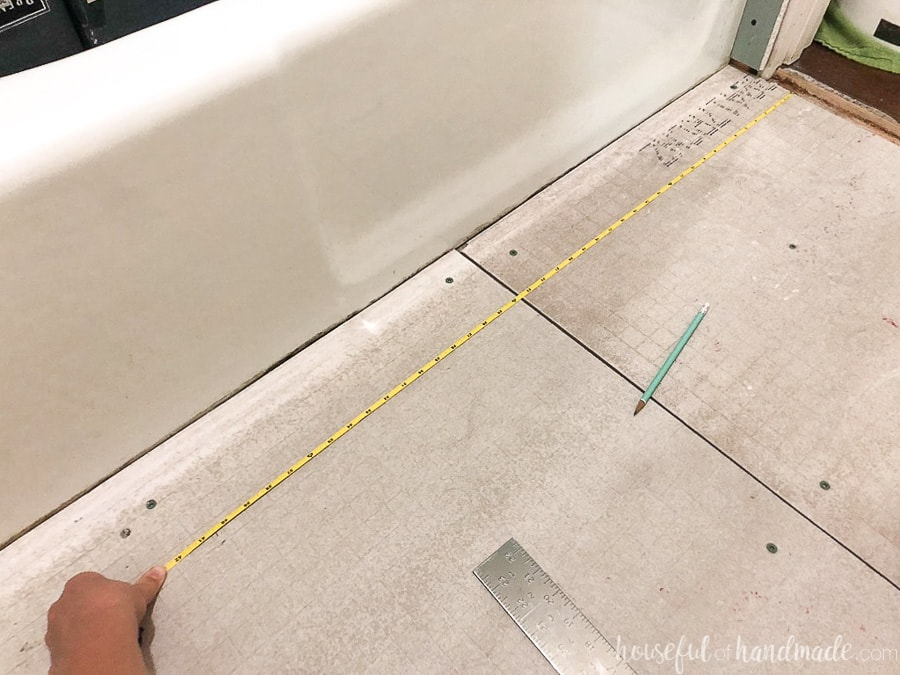 Measuring tape pulled to transfer tile layout measurement to the bathroom floor.