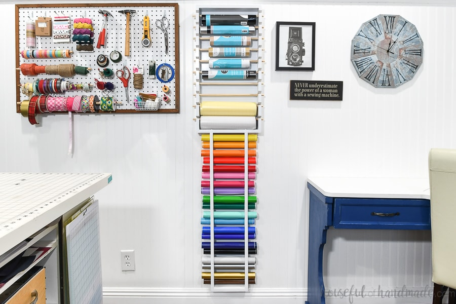 Colorful and organized craft room with storage solutions for craft supplies and vinyl rolls.