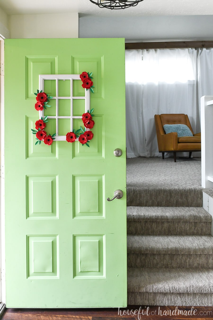 Green door with window frame wreath on it, decorated with paper poppy flowers, opening up to the house.