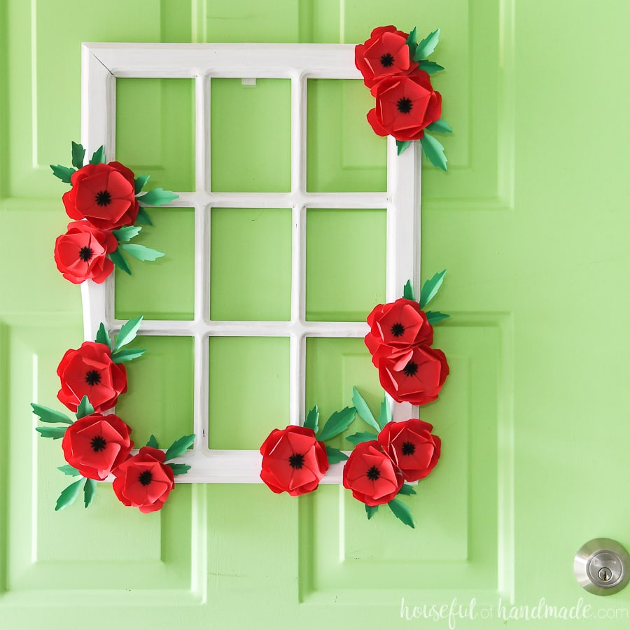 Beautiful white window frame wreath decorated with red poppies made from paper.