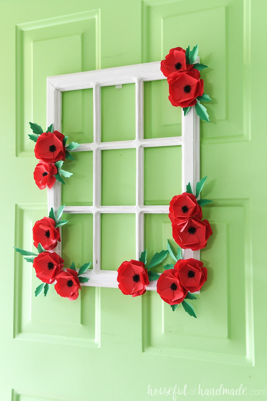 White window frame decorated with flowers to use as a wreath for the front door.