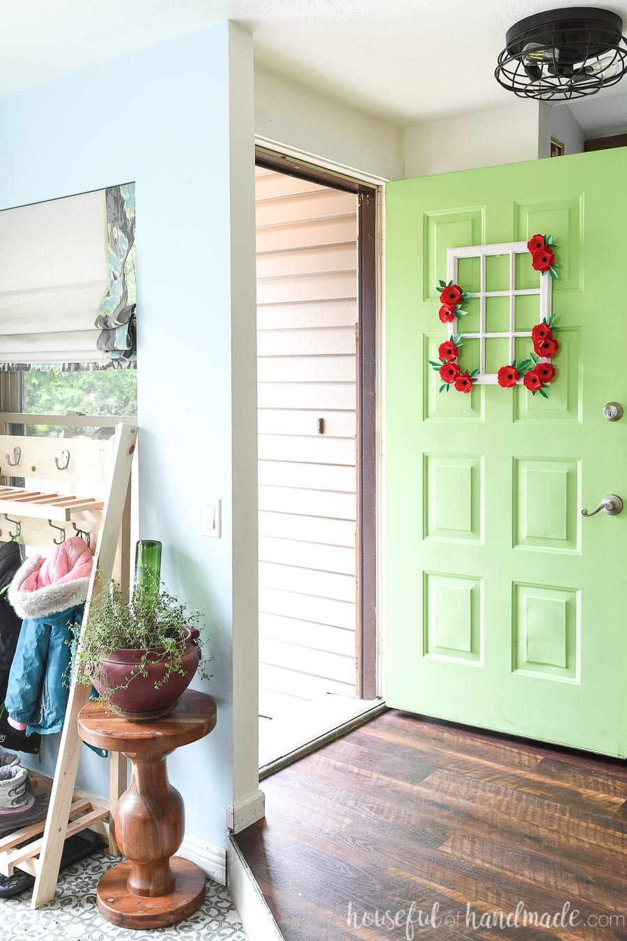 Entryway with bright green door decorated with a wreath made from a window frame.