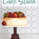 DIY cake stand made from hardwood and acrylic with a strawberry cake on top and words on it.