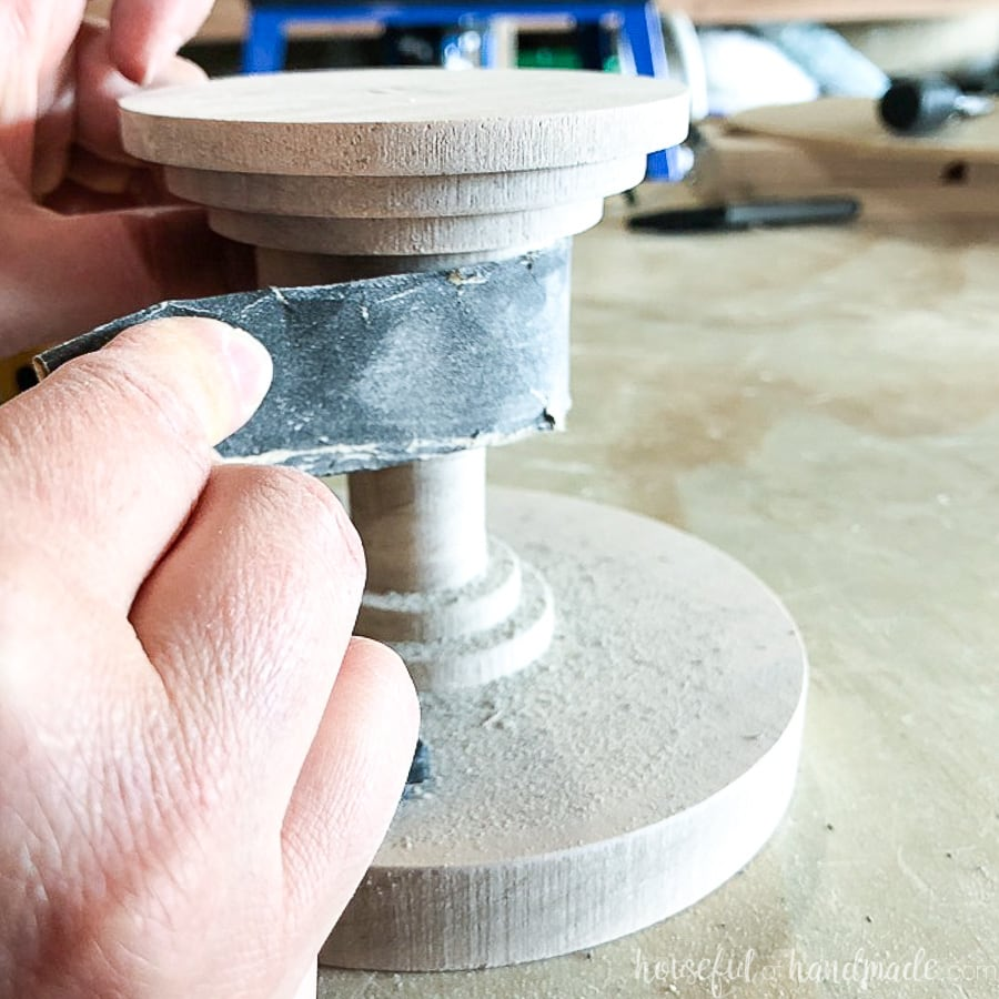Hand sanding the base of the DIY wood cake stand.
