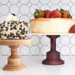 Two DIY wooden cake stands with cake on them in front of a white tile backsplash.