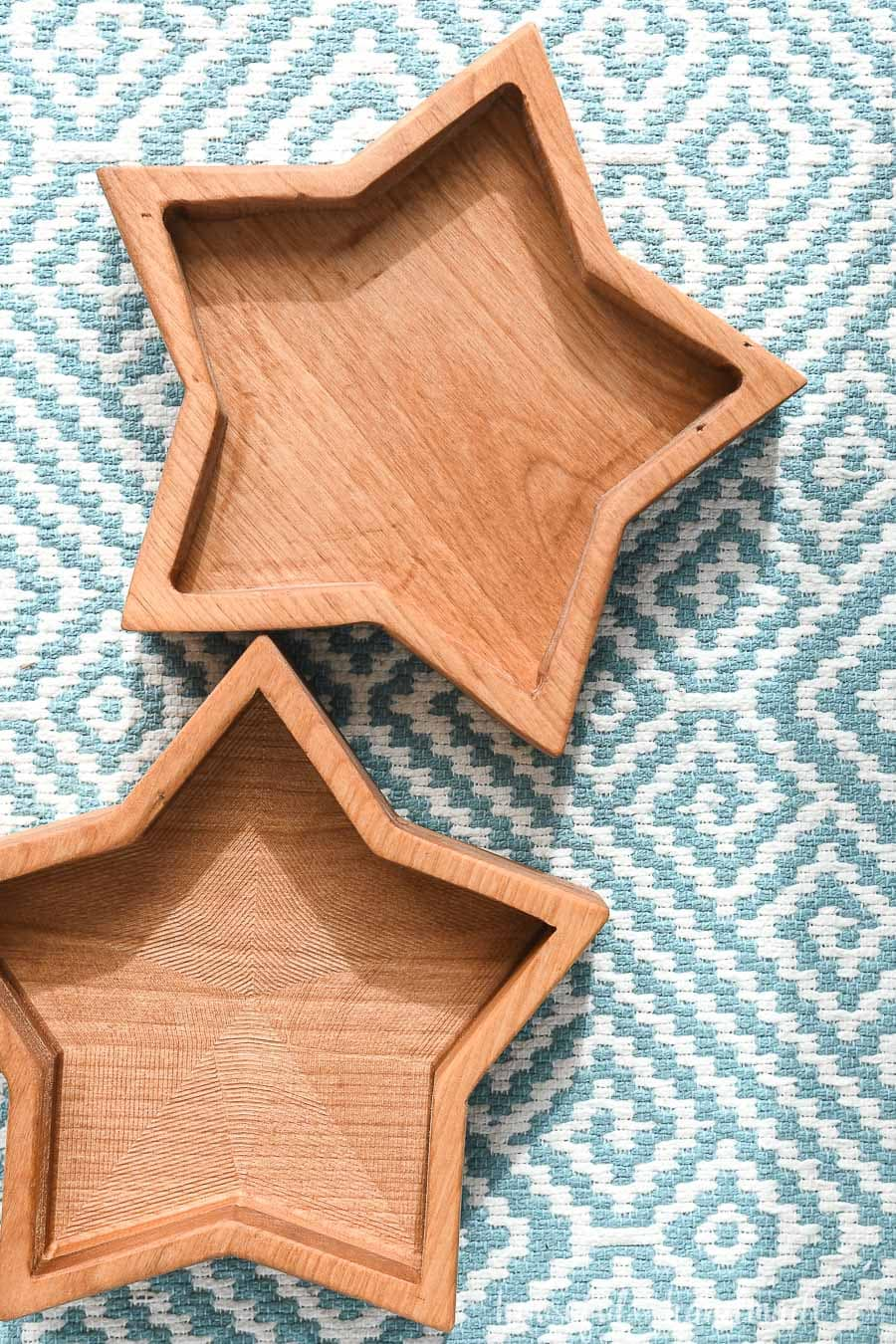 Two wooden star bowls on a blue and white placemat