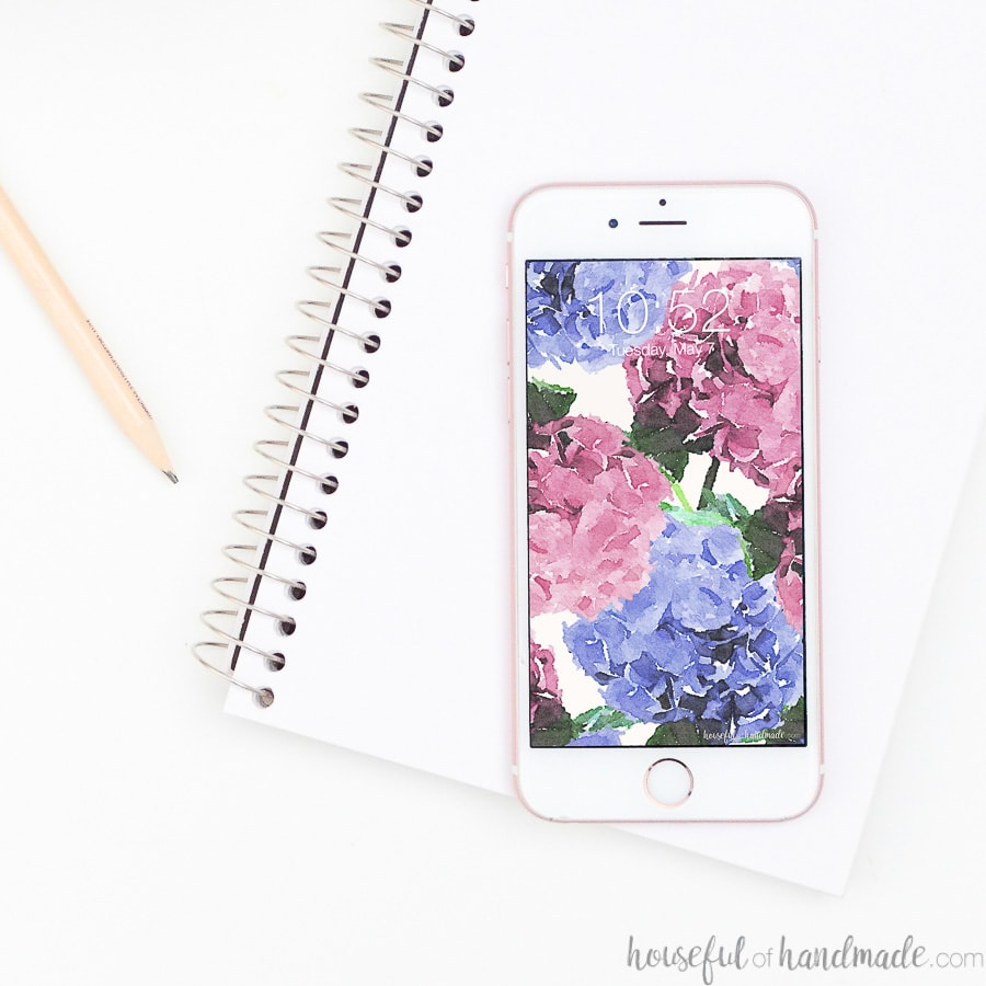 Notebook and pencil with smartphone on top of it with hydrangea free digital wallpaper design on it.