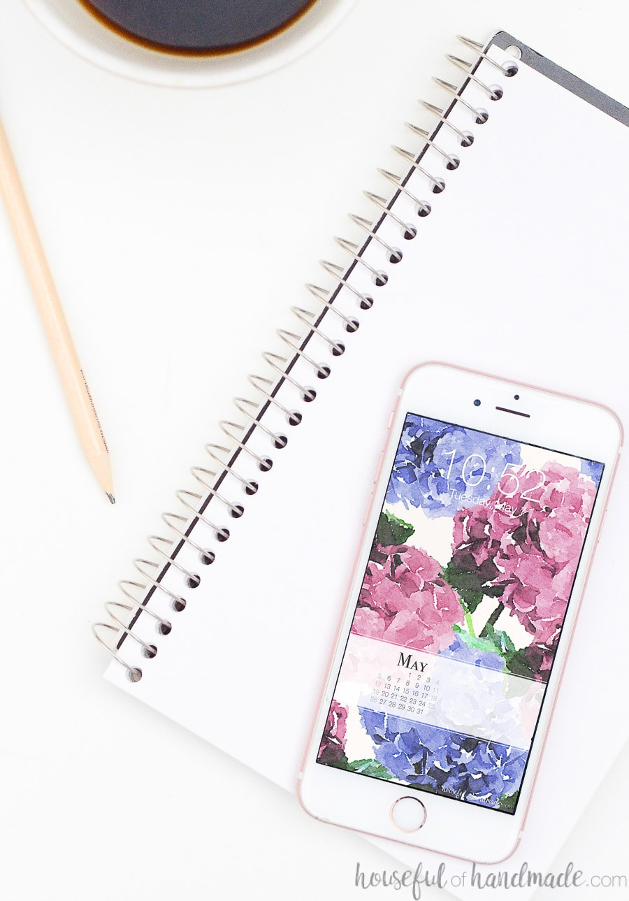 White iPhone with blue and pink hydrangea digital wallpaper design on the screen.