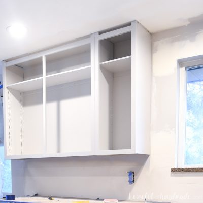 Upper kitchen cabinets painted with a light gray paint.