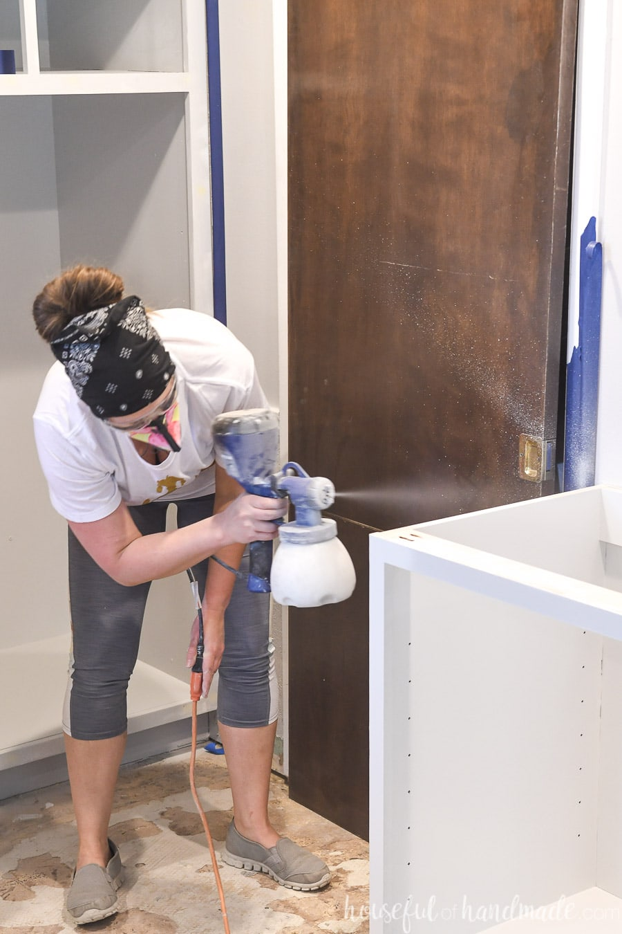 Painting kitchen cabinets with a paint sprayer.