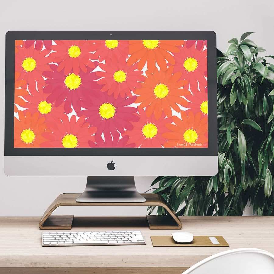 Computer on the desk with colorful floral digital wallpaper on the screen.