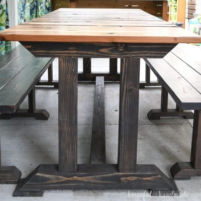 Side of the wood picnic table with dark base and redwood top.