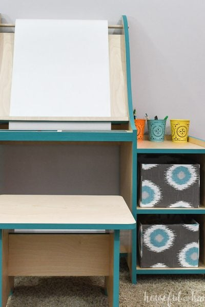 Front view of the art easel for kids with shelves for storage and bench to sit on.