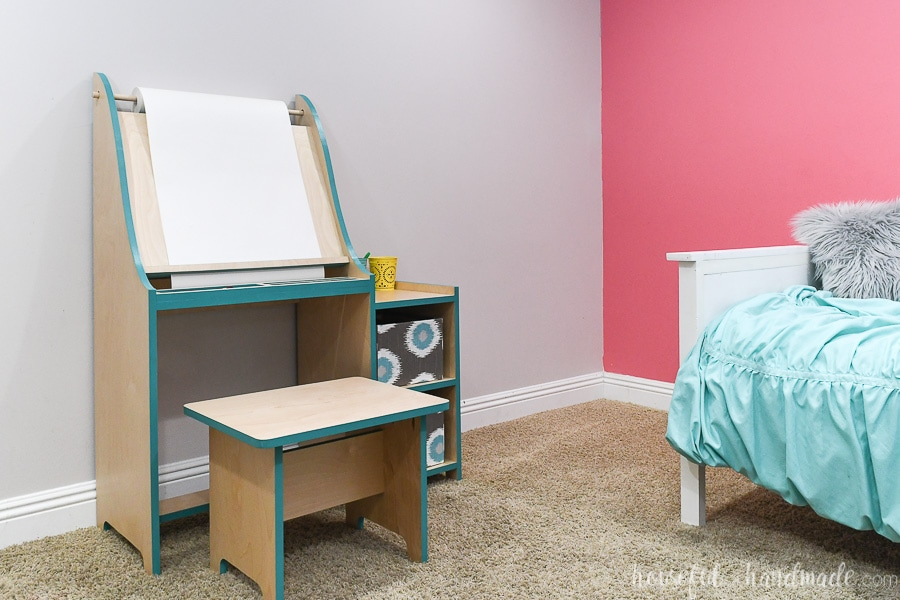 Girls bedroom with daybed on pink accent wall and kids art easel with turquoise accents on the other wall.