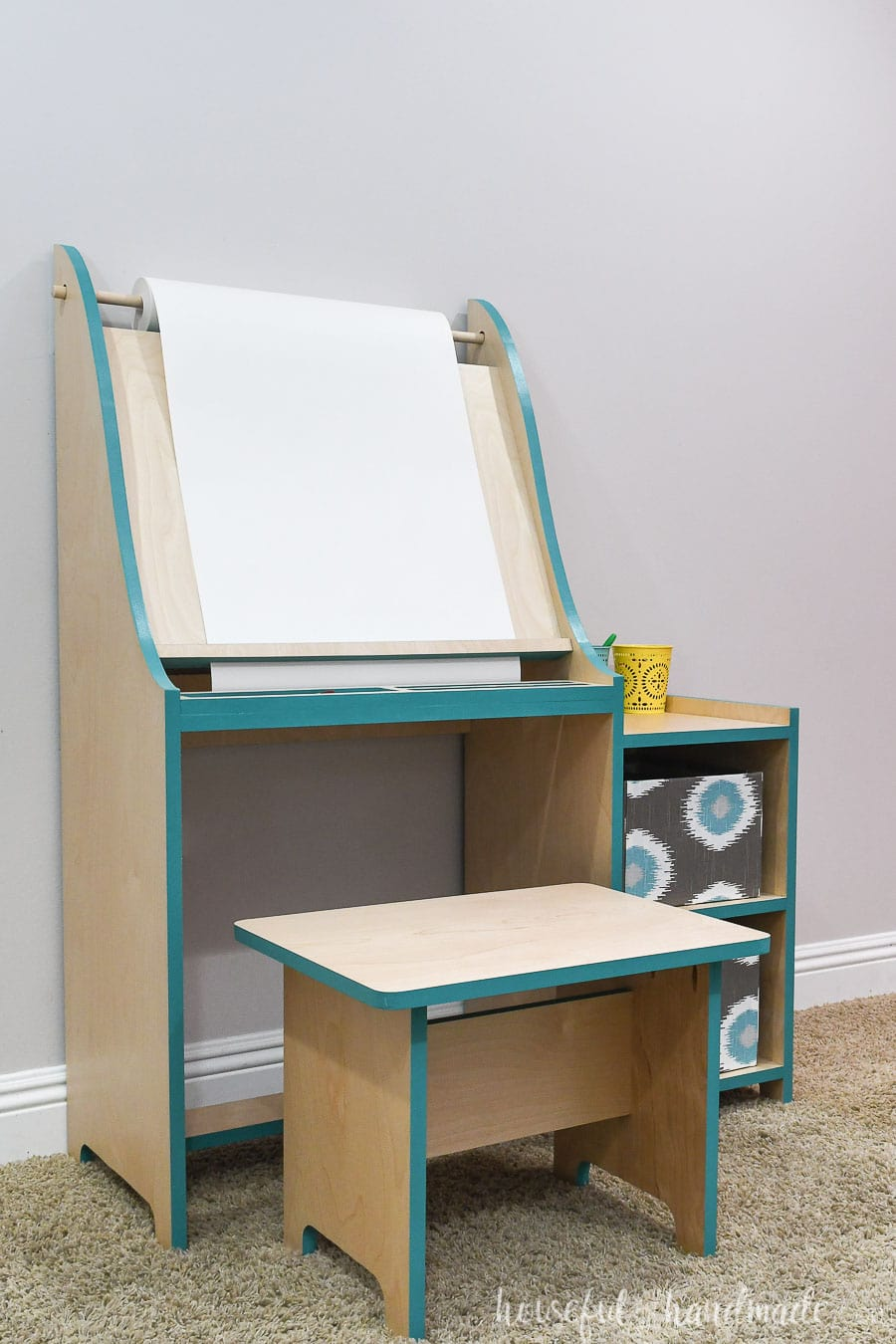 Kids art easel made from wood with shelves on the side and matching bench.