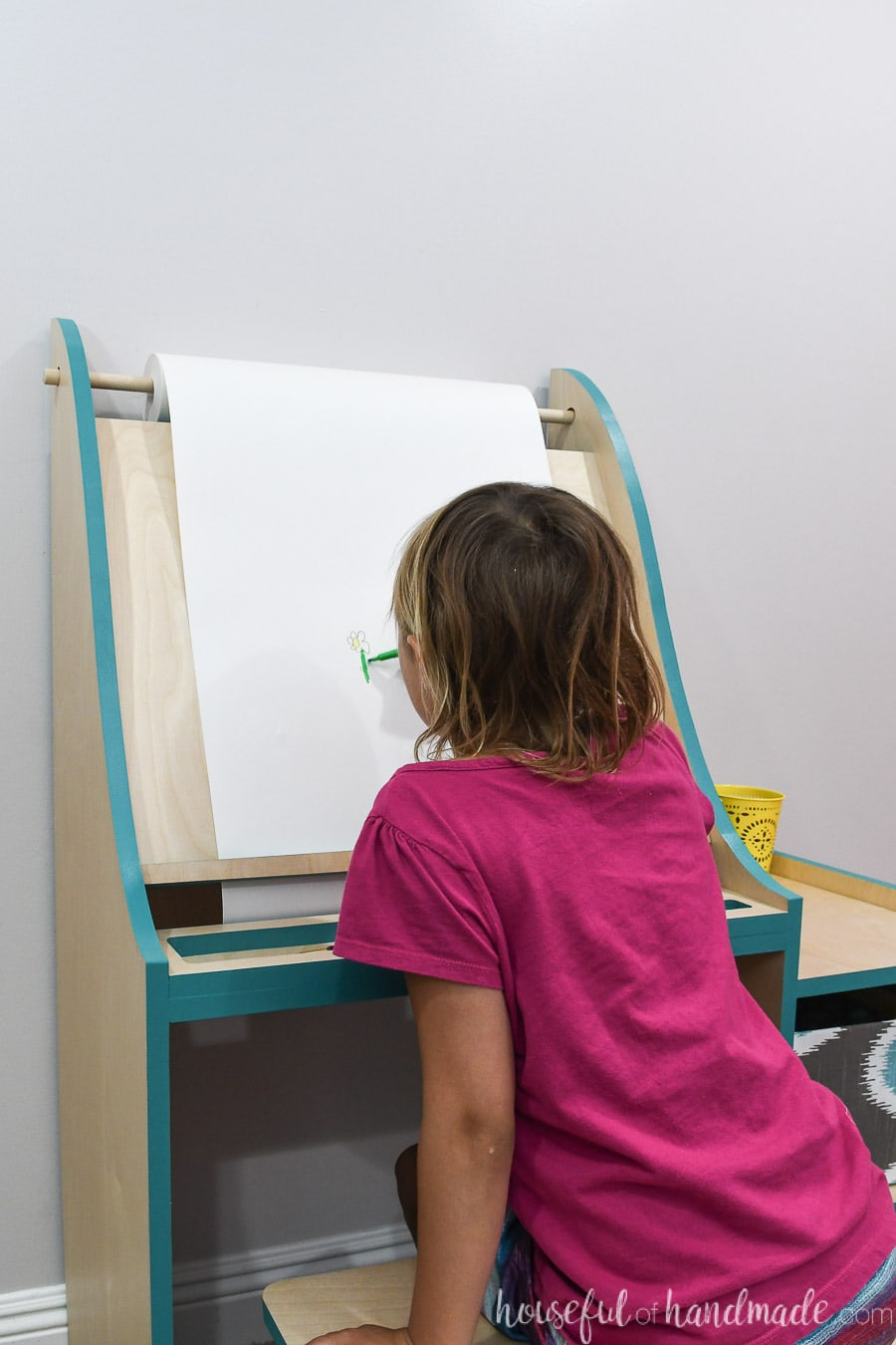 Little girl in pink shirt painting on the DIY art easel using the roll of paper.