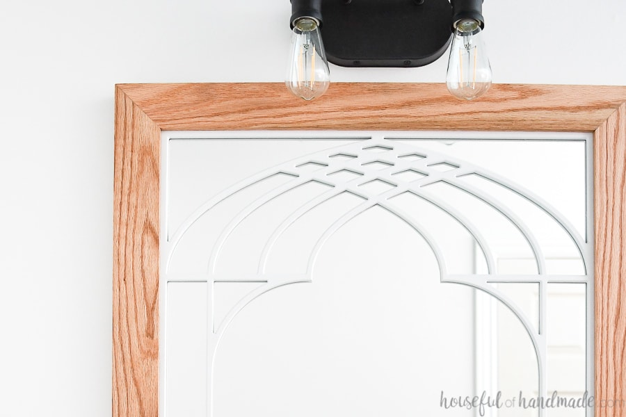 Close up of the top carved detail on the unique bathroom mirror with cathedral arch window frame design.
