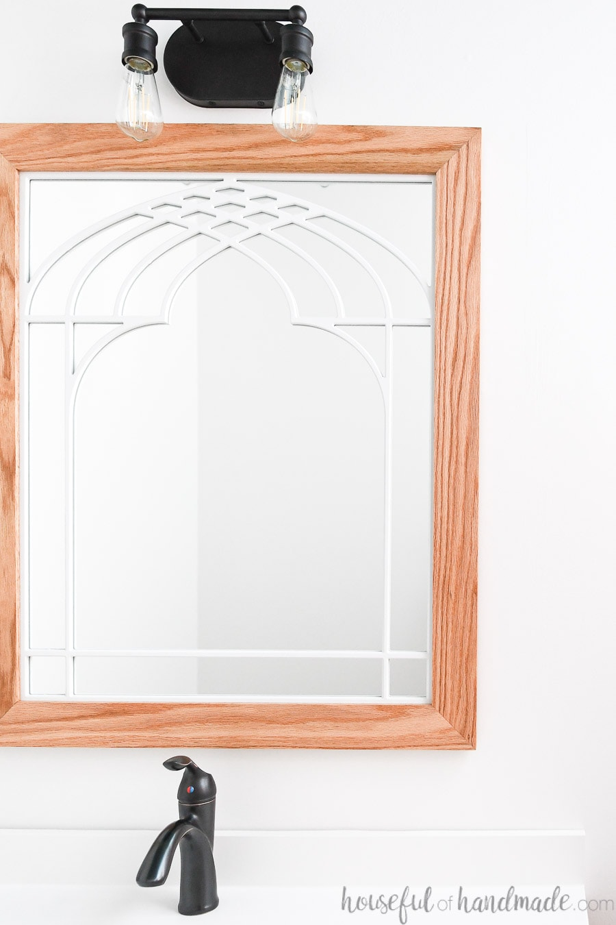 Bathroom mirror that looks like a window with cathedral arch in the center and wood frame.