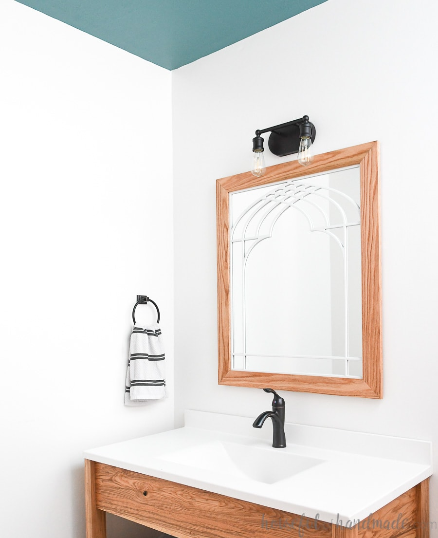 Bathroom with wood vanity, white vanity top, window frame mirror, antique bronze fixtures, and teal painted ceiling.