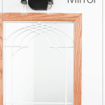 Window frame mirror in bathroom with open cathedral arch area.