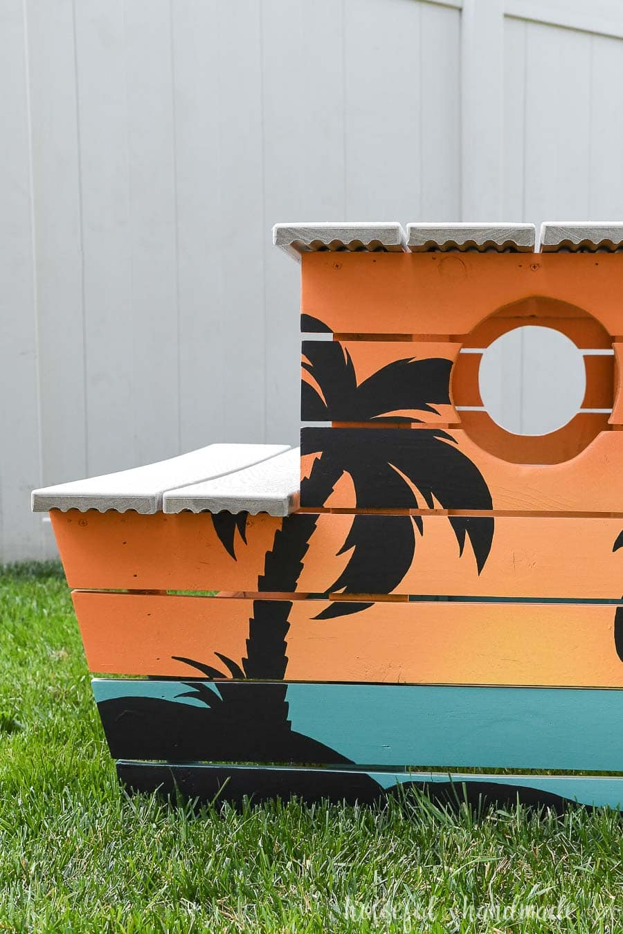Straight on view of the tropical painted picnic table with a palm tree silhouette.