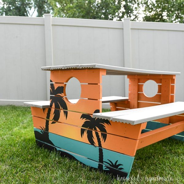 Kids picnic table with engineered decking top and seats and painted to look like a tropical sunset.