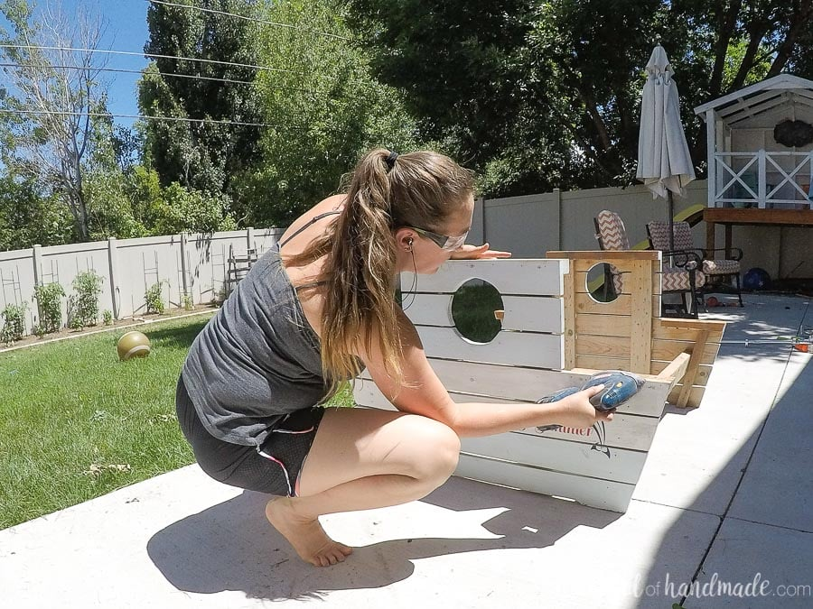 Sanding the surface of the picnic table to prepare it for the tropical paint technique.