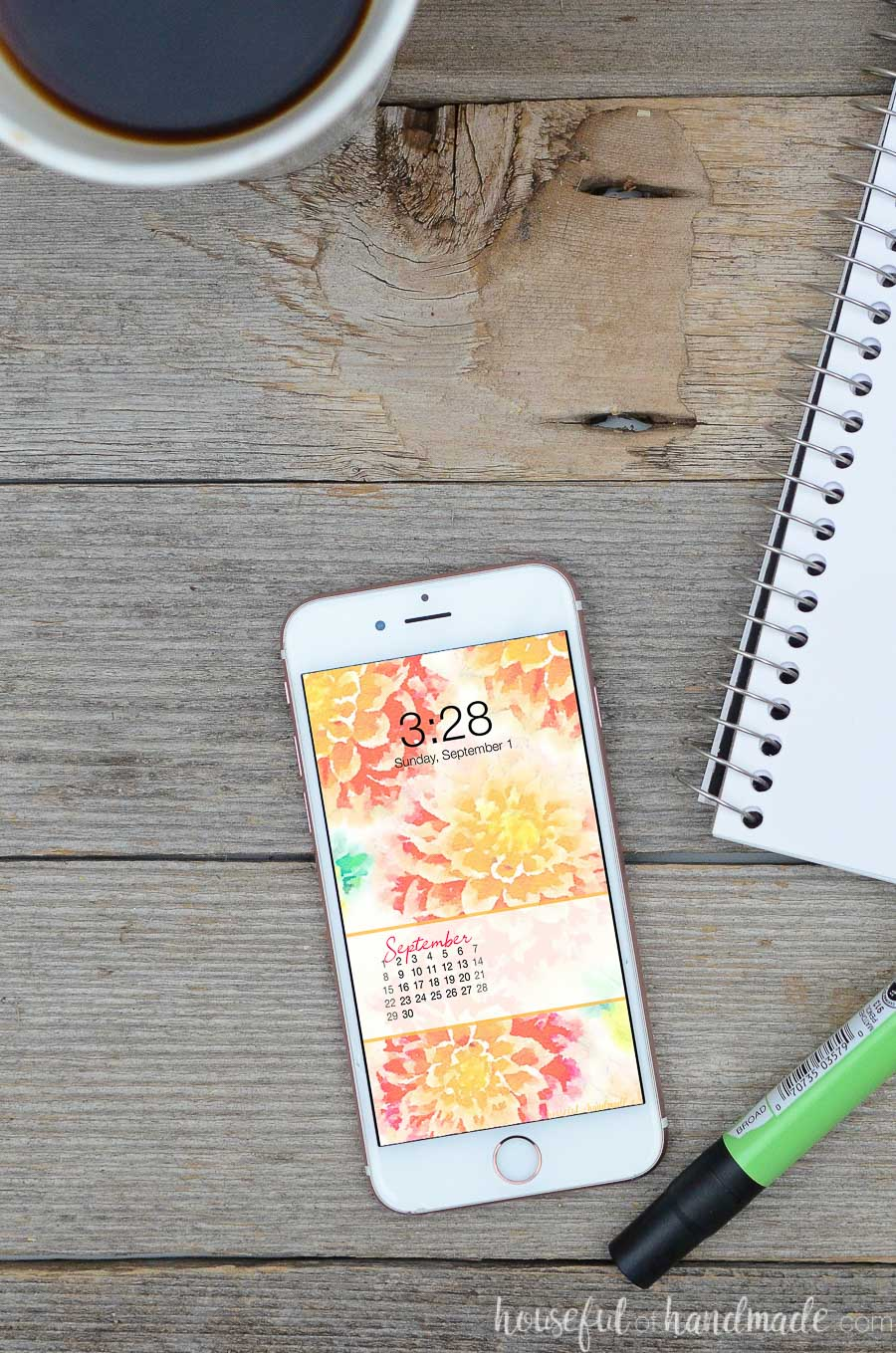 Desk with notepad, coffee, and smartphone with floral wallpaper with September calendar on the screen.